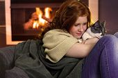 picture of fondling  - Red hair teenager girl fondling cat at home sitting by fireplace - JPG