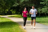 stock photo of spare  - Cheerful Caucasian couple friends running in park - JPG