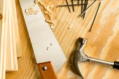 Carpenter wood saw, roofing hammer, nails and slats