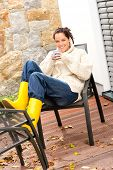 Cheerful woman drinking tea cup veranda autumn relaxing