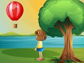 Illustration of a girl watching the hot air balloon at the riverbank