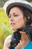 Athletic woman adjusting her bike helmet in the countryside