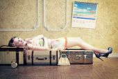 young woman, sleep on the luggage, waiting her vacation