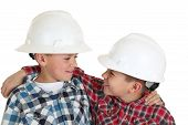 Two Boys Hugging Wearing Construction Hardhats Smiling