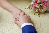 Hands Of A Bride And A Bridegroom, Just Married, A Bridal Bouquet Is Beside