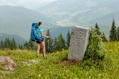 Hiker In Carpathian Mountains Near Frontier Stone