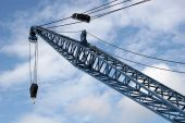 stock photo of crane hook  - arm of crane on dock against blue sky - JPG