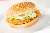 stock photo of sesame seed  - Crispy chicken burger on a white plate close up - JPG