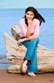 Beautiful Biracial Teen Girl Sitting On Fallen Log By Lake Shore In Summer
