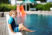Cute Toddler Playing With Water By The Outdoor Swimming Pool