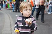 Little Boy Of Three Years Eating At A Funfair, Outdoors