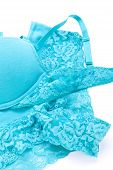 foto of frilly  - Set of sexy turquoise blue lingerie with a bra and pair of cute frilly pants with floral patterned lace isolated on white - JPG