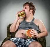 stock photo of beef-burger  - Fat man eating hamburger seated on armchair - JPG