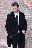 young business man posing outdoor with a hand in his pocket and the other on his overcoat while look