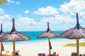 beautiful beach with deckchairs and straw umbrellas in mauritius