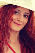 Beautiful young caucasian redhead woman in swimsuit and hat