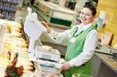 Smiling saleswoman assistant in supermarket working with scales balance to pregnant female customer