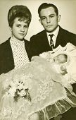 LODZ, POLAND,CIRCA SEVENTIES- vintage photo of godparents with a baby in traditional baby's sleeping bag for christening