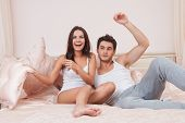 pic of pillow-fight  - Young couple fighting pillows in the bedroom - JPG