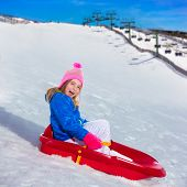 Kid girl playing sled in snow with winter wool pink hat [photo illustration]