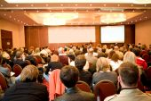 stock photo of audience  - Rear view of many listeners sitting on chairs during lecture at conference - JPG