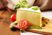 Tasty Camembert cheese with tomatoes, olives and basil, on wooden table