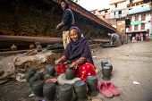 BHAKTAOUR, NEPAL - DEC 7, 2013: Unidentified Nepalese woman working in the his pottery workshop. Mor