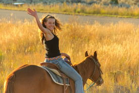 picture of horse girl  - Teen riding on a horse away from home   - JPG
