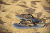Blue Plastic Thongs In The Sand