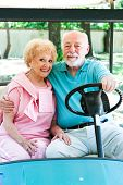 Senior couple uses a golf cart for transportation in their adult community.