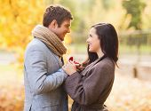 love, relationship, family and people concept - close up of smiling couple with red gift box in autu