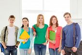 education and school concept - group of smiling students with bags and folders at school