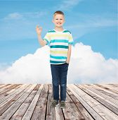 happiness, childhood and people concept - smiling little boy in casual clothes making ok gesture ove