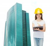 childhood, construction, architecture, building and people concept - smiling little girl in protecti