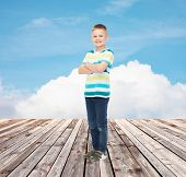 happiness, childhood, summer and people concept - smiling little boy in casual clothes over blue sky