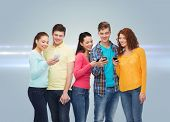 friendship, technology and people concept - group of smiling teenagers with smartphones over gray ba