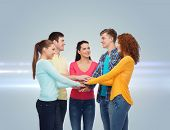 friendship, teamwork, gesture and people concept - group of smiling teenagers with hands on top of e