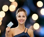 shopping, wealth, money, luxury and people concept - smiling woman in evening dress holding credit c