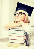 business and education concept - happy student in graduation cap with stack of books