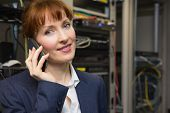 Pretty computer technician talking on phone beside open server in large data center