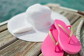 beach, summer, vacations and accessories concept - close up of hat, sunscreen and slippers at seaside