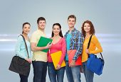 friendship, future, education and people concept - group of smiling teenagers with folders and school bags over gray background with laser light