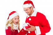 Festive young couple exchanging presents on white background