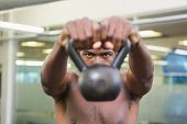 Close-up portrait of a shirtless muscular man lifting kettle bell in the gym
