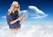 Smiling trendy blonde using tablet computer against bright blue sky with clouds