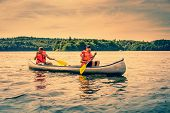 pic of canoe boat man  - Men sailing a canoe wearing orange lifejackets - JPG