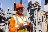 stock photo of electrical engineering  - handsome young african electrical engineer holding clipboard in power station - JPG
