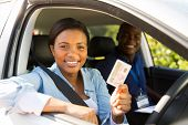 african student driver passes driving test and holding her driver's license