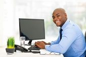 cheerful young black businessman using computer in office