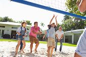 Multi Generation Family Playing Volleyball In Garden